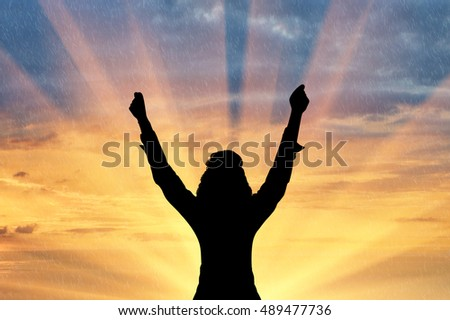 Emotion of happiness. Silhouette of a happy man with his hands raised in the sunset background