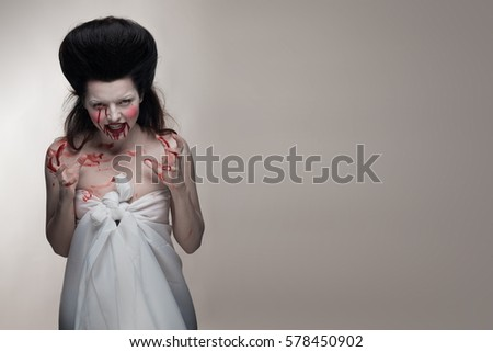 emotional actress brunette woman with pale skin as a vampire with blood on her face on a white background in studio