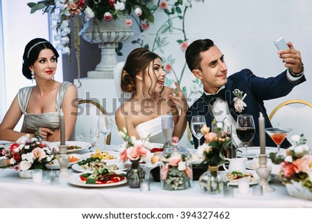 Emotional beautiful newlywed couple taking selfie at wedding reception - stock photo