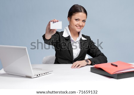 Emotional business woman in office palce show white personal card. Smile - stock photo