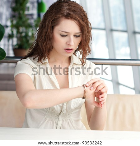 Emotional business woman with watch at office
