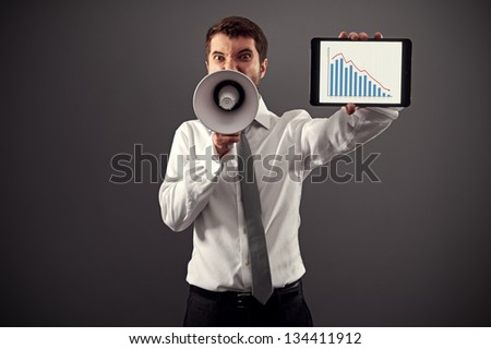 emotional businessman showing the business graph and shouting with megaphone against grey background - stock photo