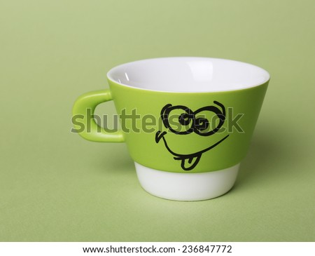 Emotional cup on green background - stock photo