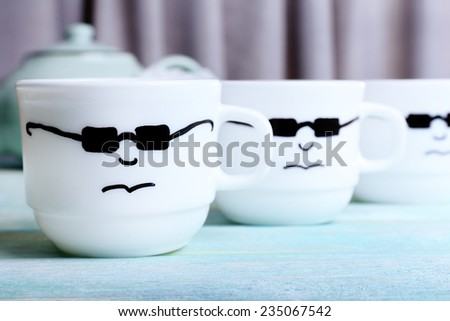 Emotional cups on wooden table - stock photo