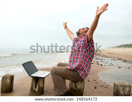 Emotional elderly businessman with laptop on the beach