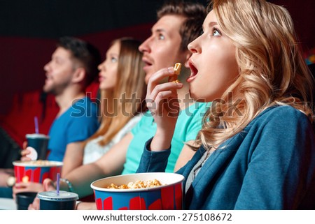 Emotional film. Excited blond woman eating popcorn emotionaly in cinema near other viewer. - stock photo