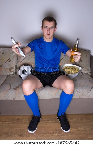 emotional football supporter watching tv with bottle of beer and chips - stock photo