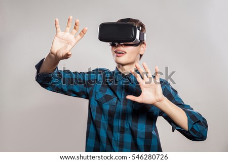 emotional funny man wearing virtual reality goggles. Studio portrait of video game designer wearing VR headset. studio shot isolated on gray background.