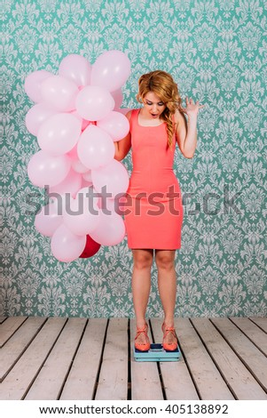 Emotional girl in retro style is on the scales with balls - stock photo