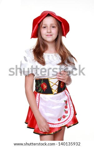 Emotional little girl dressed as fairy-tale characters in a red hat on a white background on Holiday/Caucasian girl with a sweet smile in a beautiful dress and red hat