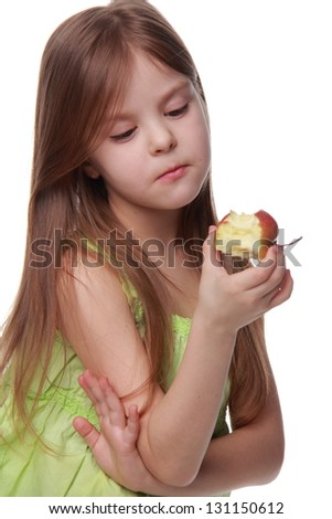 Emotional little girl eats an apple for health/Girl in casual clothes eating an apple on white background on Food and Drink