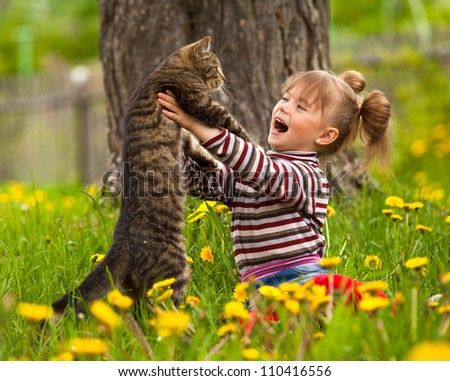 Emotional little girl playing with a cat in the park. - stock photo