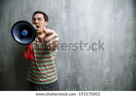 Emotional man yells into a megaphone and points on the background of gray wall texture. - stock photo