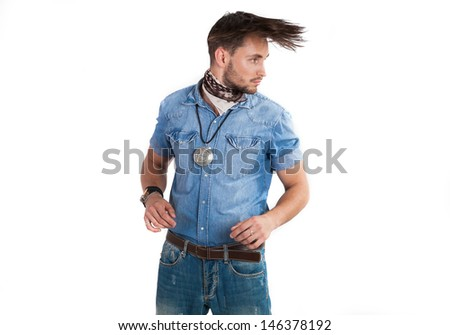 Emotional portrait of a handsome sexy man with long hair on a white background. Dynamic man in a denim shirt and trousers.