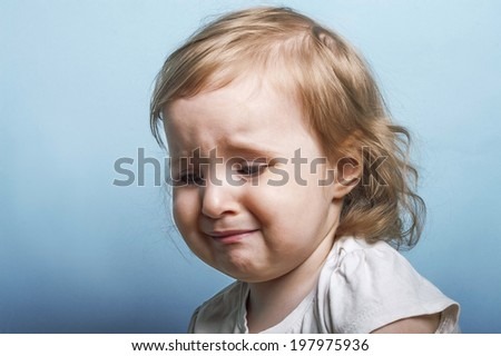 Emotional portrait of a two years old girl ready to burst to cry, blue background studio shot - stock photo