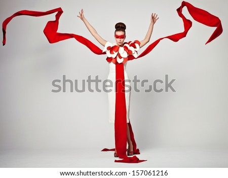 emotional portrait of fashion woman in exclusive dress posing in studio , textile is flying