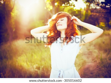 Emotional portrait of happy beautiful woman with red curly hair and natural makeup enjoying her life in nature. Soft sunny colors. Outdoor shot. Copyspace. - stock photo