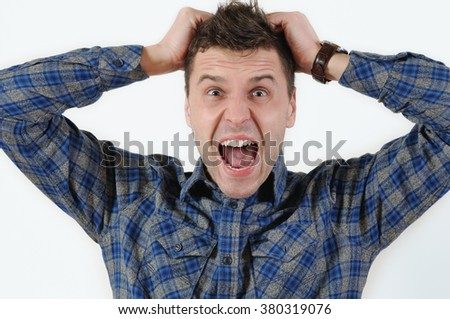 emotional portrait of young angry screaming man pulling his hair. Human emotion facial expression feeling - stock photo