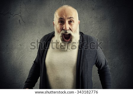 emotional screaming senior man with beard over dark wall - stock photo