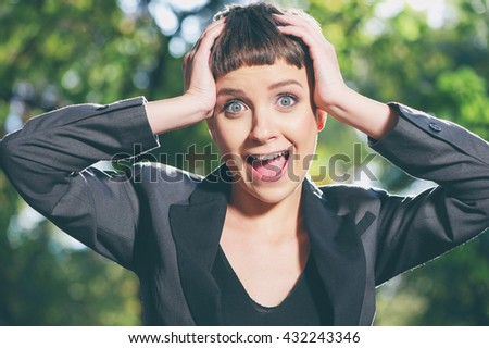 Emotional stress. Stressed businesswoman. Frustrated caucasian young woman in formalwear holding head in hands and looking at camera while standing outdoors - stock photo