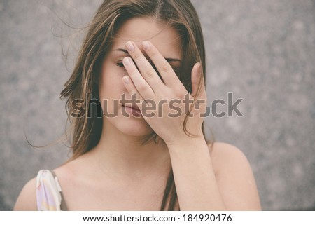 emotional stress ,woman with hand covering  the eyes, selective focus - stock photo