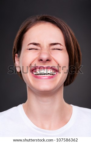 emotional woman is laughing loudly over dark background - stock photo