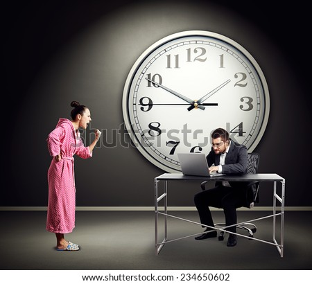 emotional woman screaming at busy businessman over dark wall with big clock - stock photo