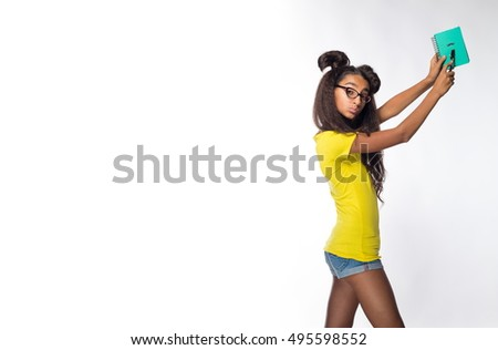 Emotional young brunette girl with long hair in yellow shirt and glasses with notepad in hand on white background