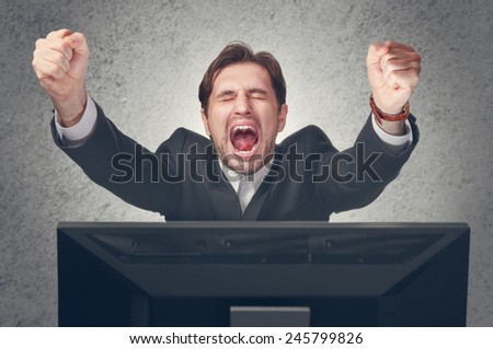 emotional young businesman rejoices win at the computer - stock photo