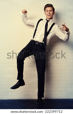 Emotional young man in elegant suit posing by white brick wall. - stock photo