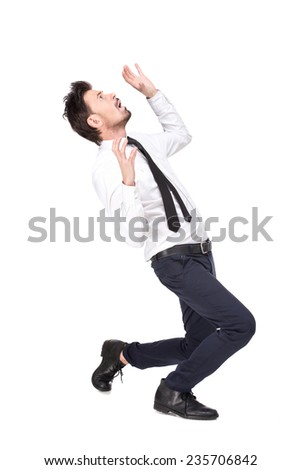 Emotional young man in position, emotion of fear, isolated on gray background. - stock photo