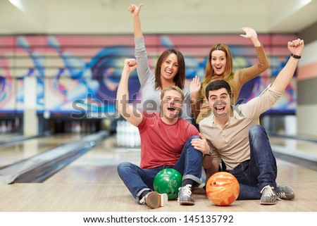 Emotional young people in bowling - stock photo