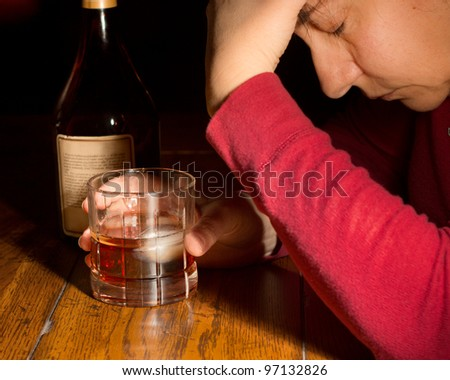 Emotionally distraught woman with a glass of whiskey and bottle - stock photo