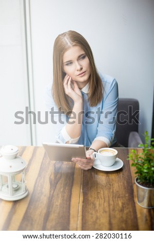 Emotionless woman surfing the net in cafe