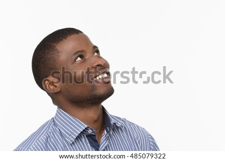 Emotions concept. Portrait of Afro-American man happy smiling and looking upwards while posing isolated on white background in studio.
