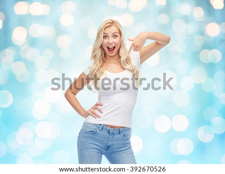 emotions, expressions, advertisement and people concept - happy smiling young woman or teenage girl in white t-shirt pointing finger to herself over blue holidays lights background