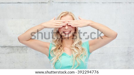 emotions, expressions and people concept - smiling young woman or teenage girl covering her eyes with palms over gray concrete wall background - stock photo