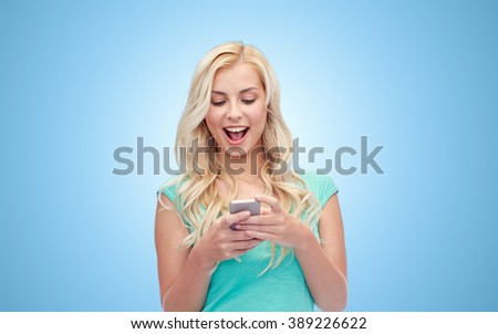 emotions, expressions, technology and people concept - smiling young woman or teenage girl texting on smartphone over blue background - stock photo