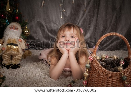 emotions of the nice girl which lies near a New Year tree  - stock photo