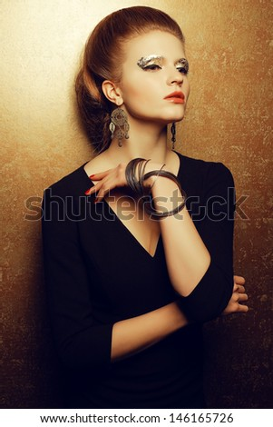 Emotive portrait of a beautiful fashion red-haired model with a great makeup of golden foil posing over golden background. Vintage accessories (earrings and bracelet). Retro style hairdo. Studio shot - stock photo