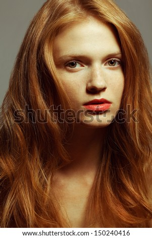Emotive portrait of a fashionable model with red (ginger) curly hair and natural make-up posing over grey background. Perfect skin with freckles. Retro style. Close up. Studio shot - stock photo