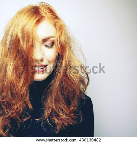Emotive portrait of a fashionable model with red (ginger) wavy hair and natural make-up. White shiny smile. Perfect skin with freckles. Close up. Studio headshot. Photo toned style instagram filters - stock photo