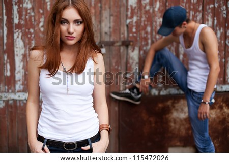 emotive portrait of a stylish couple in jeans standing near wooden house. outdoor shot