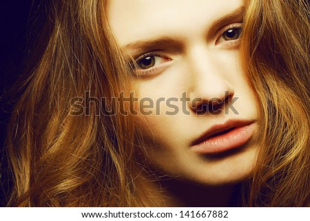 Emotive portrait of a young beautiful girl with long ginger (red) hair posing over black background. Perfect skin and hair. Spa salon. Close up. Studio shot