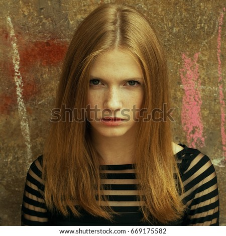 Emotive portrait of a young beautiful red-haired girl wearing trendy black cocktail dress and posing over wall with chalk drawings. Fashion style. Healthy skin with freckles, glossy hair. Outdoor shot