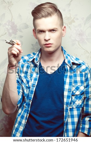 Emotive portrait of a young fashionable hipster boy smoking too many cigarettes over vintage background. Trendy casual clothes. Perfect glossy blond hair. Studio shot - stock photo