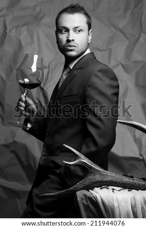 Emotive portrait of handsome stylish man in elegant dark gray suit drinking red wine. Baroque accessories: deer horn, grey and white cloths. Retro and Vogue style. Studio shot