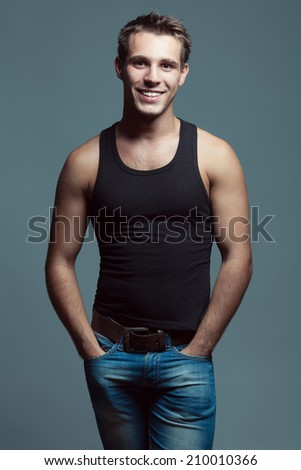 Emotive portrait of handsome young man looking at camera with arms in pockets of blue jeans, posing over gray background. White shiny smile, great muscles and healthy skin. Urban style. Studio shot - stock photo