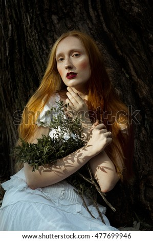 Emotive portrait of Young ginger woman with blue eyes in a white dress, seating near the tree. Holding bouquet of branches with green leaves