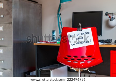 Employee leaves note on back of office chair: Out of Office. Gone on Vacation! - stock photo